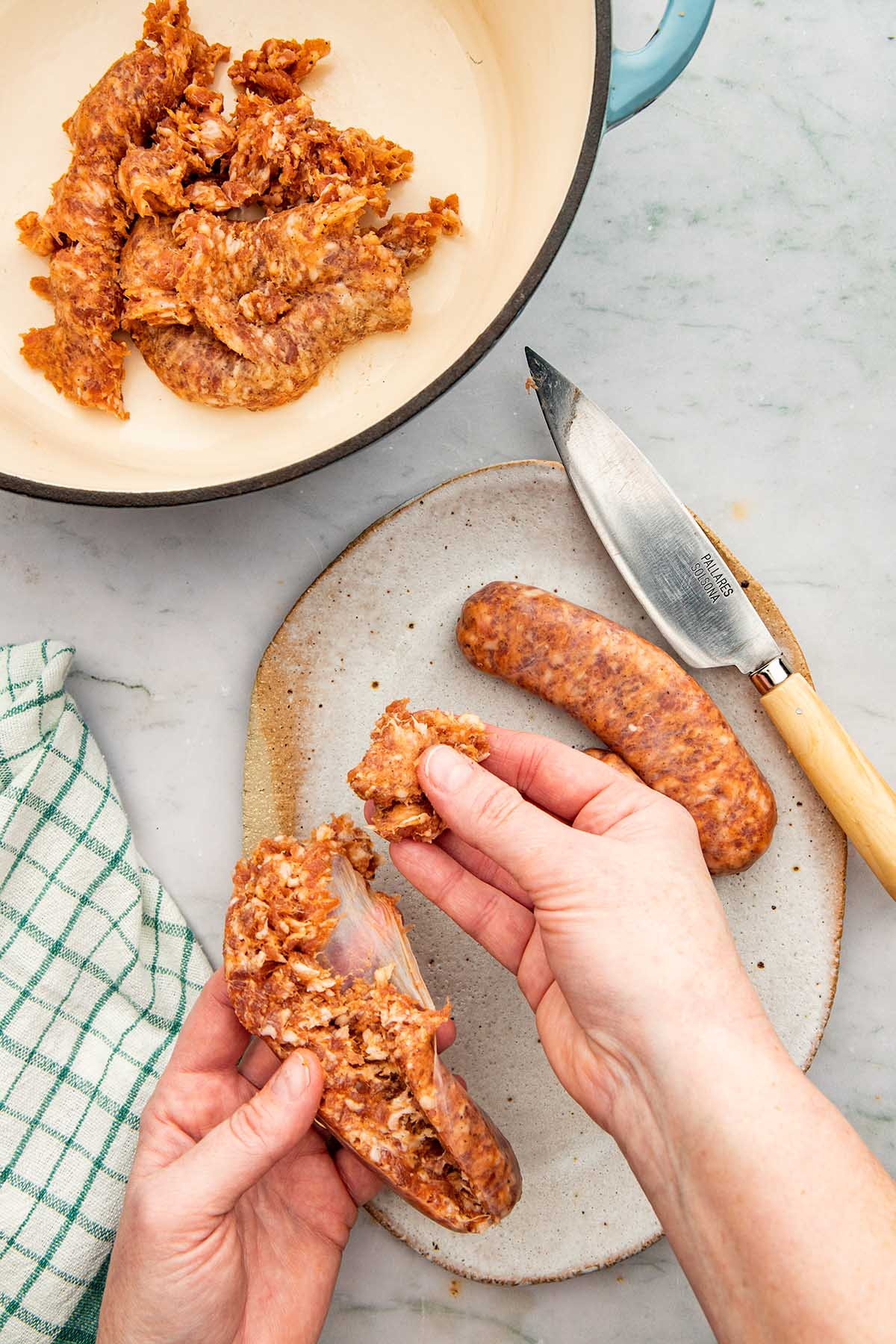 A hand removing sausage meat from a sausage casing.