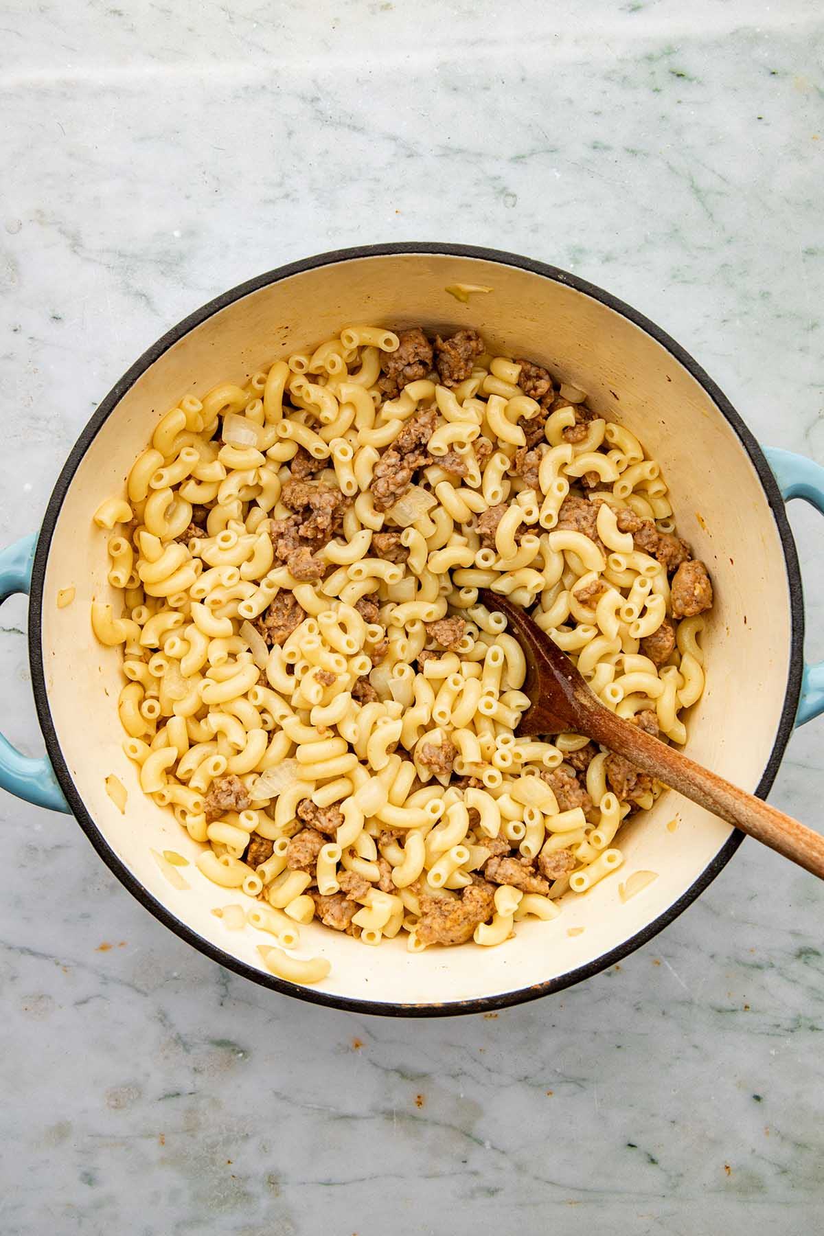Cooked sausage and macaroni noodles stirred together in a pot.