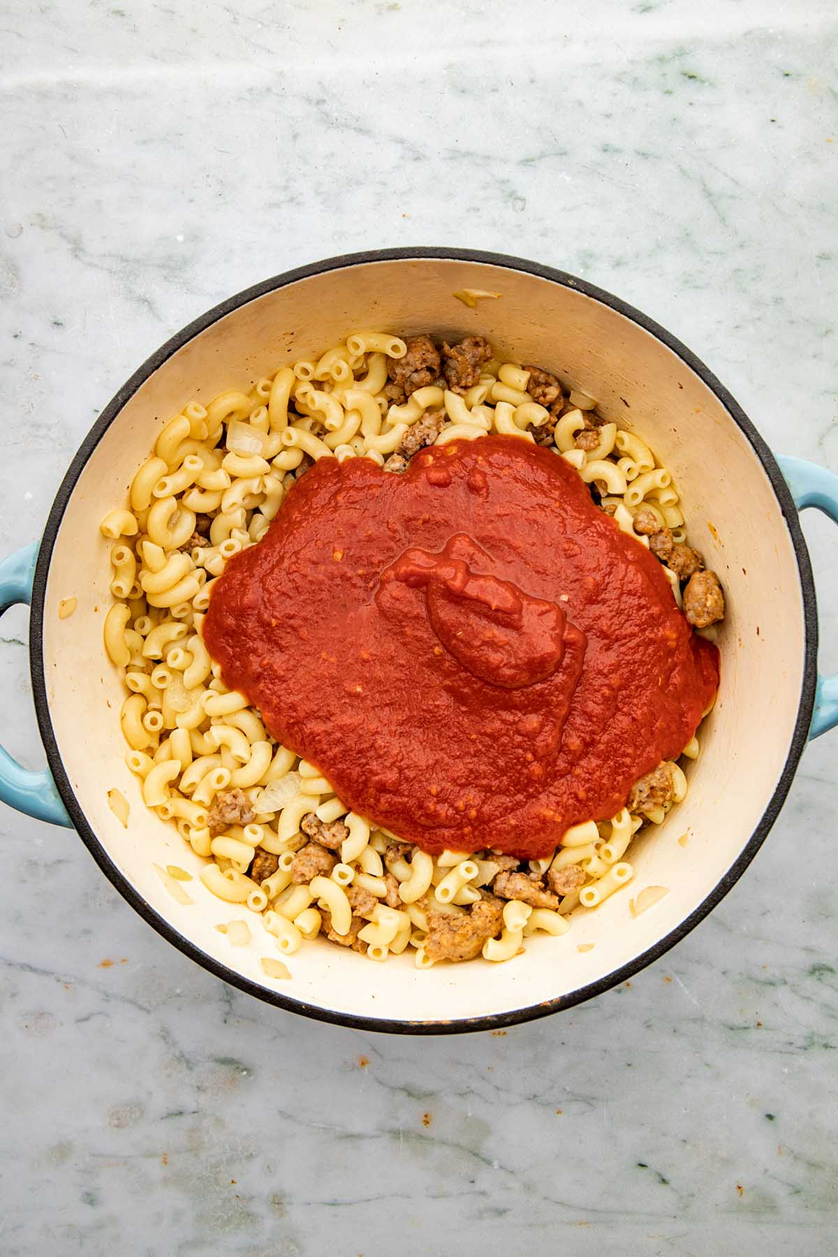 A pot of cooked macaroni noodles, sausage, onion, and tomato sauce, unmixed in a blue pot.