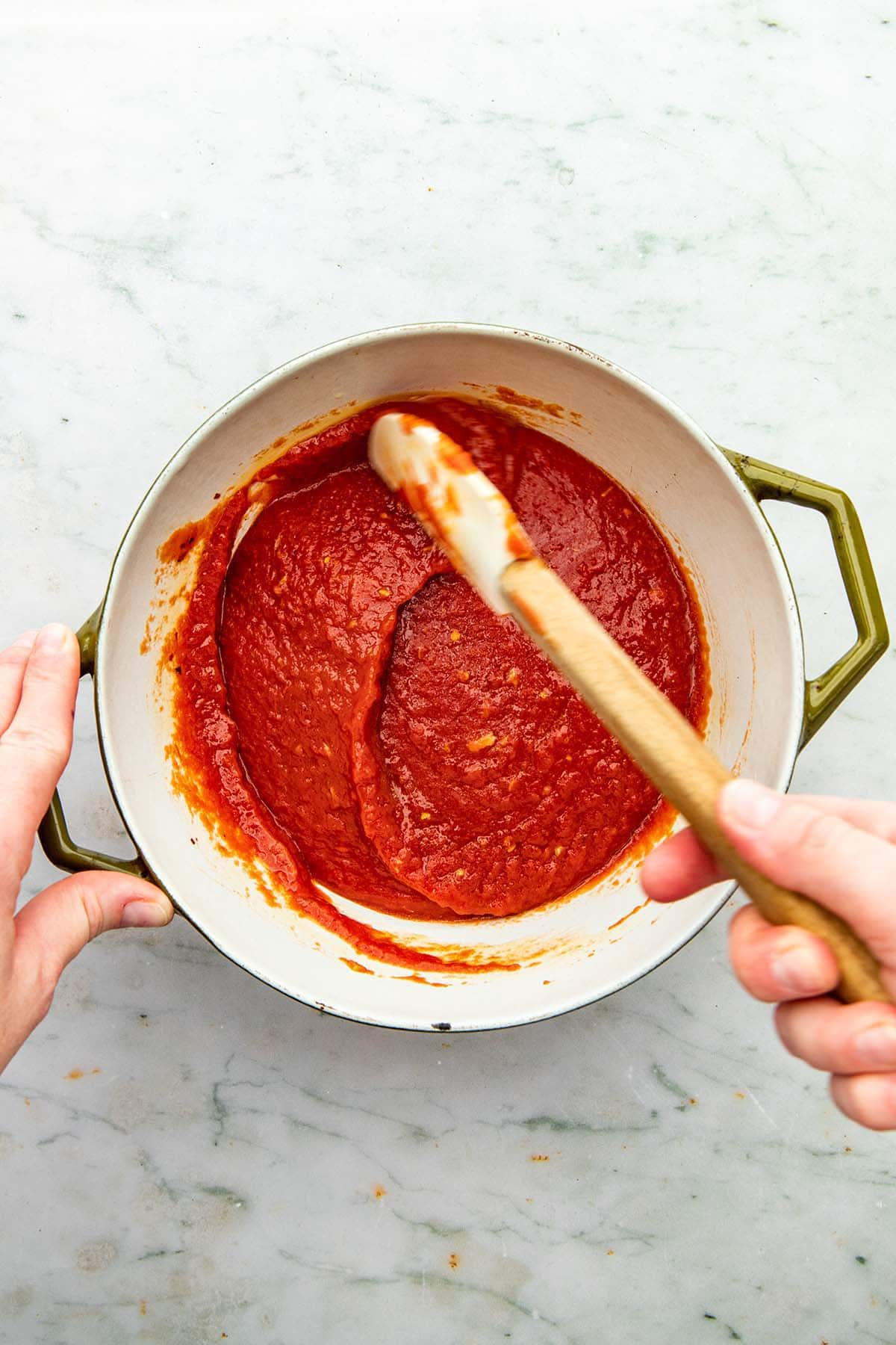 A hand stirring tomato sauce in a pot with a rubber spatula.