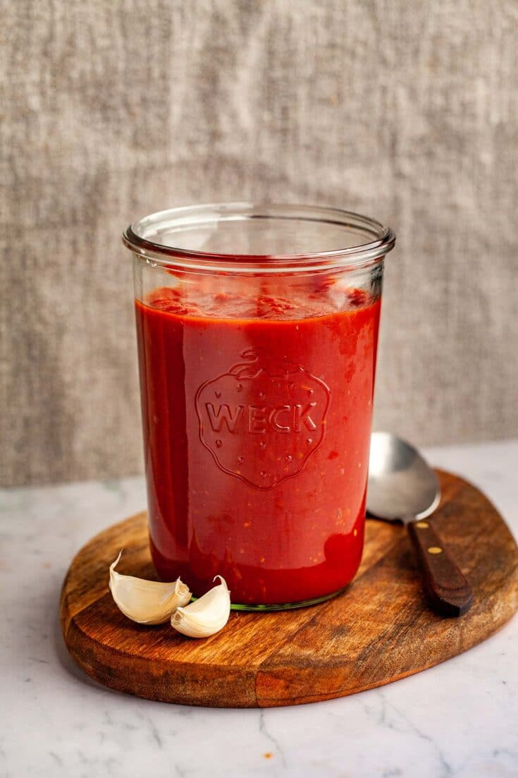 A tall jar of homemade tomato sauce on a wood board with a spoon and two garlic cloves nearby.