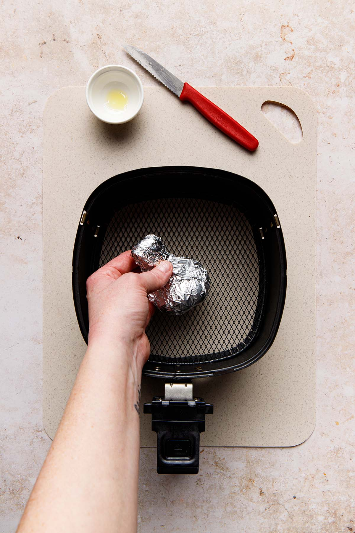 A hand placing a small item, wrapped in aluminum foil, inside the basket of an air fryer.