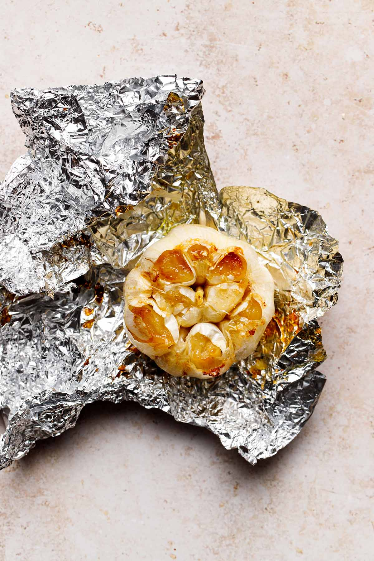 A bulb of air fryer roasted garlic sitting on the piece of aluminum foil it was cooked in.