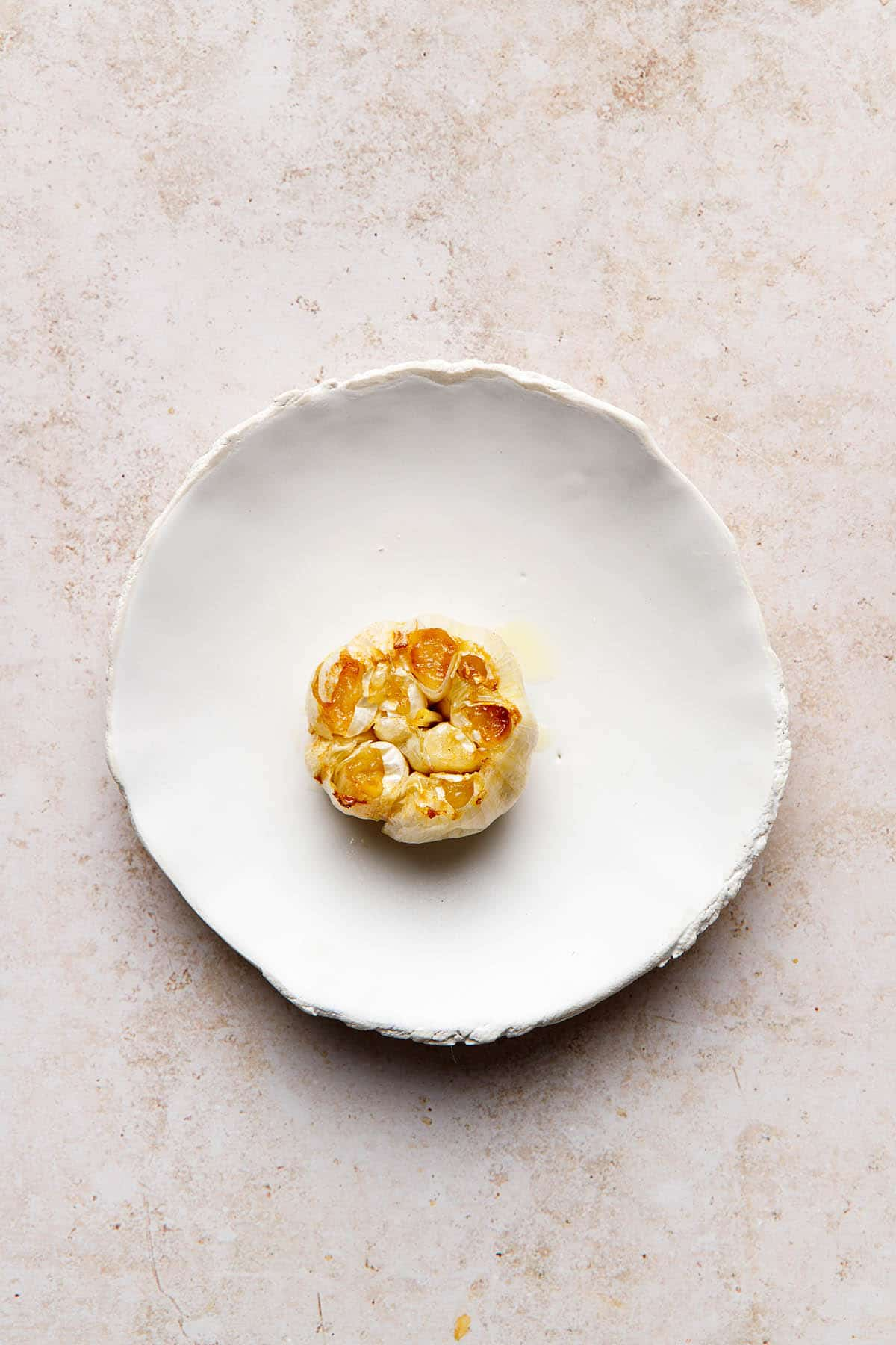 A bulb of air fryer roasted garlic on a white porcelain plate.