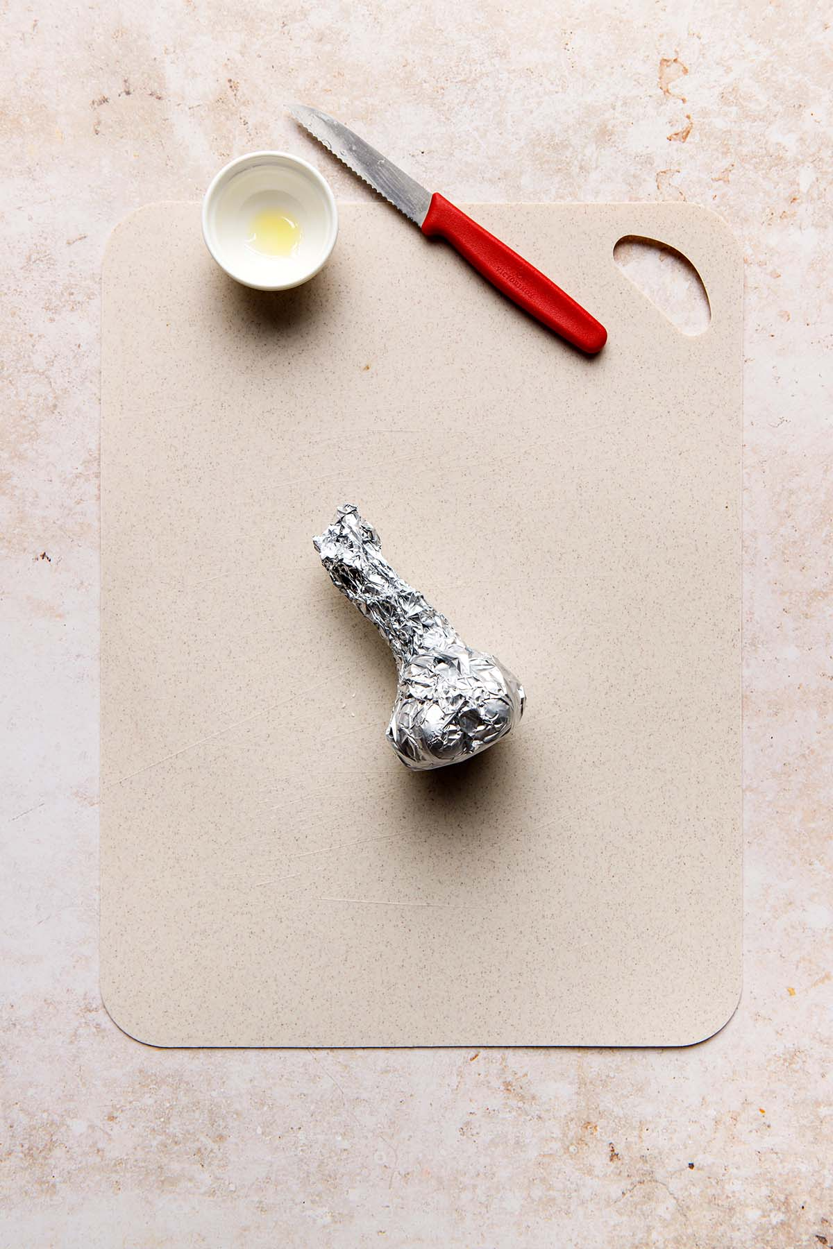 A bulb of garlic wrapped in foil laying on a beige cutting board with a small white bowl and red-handled knife nearby.