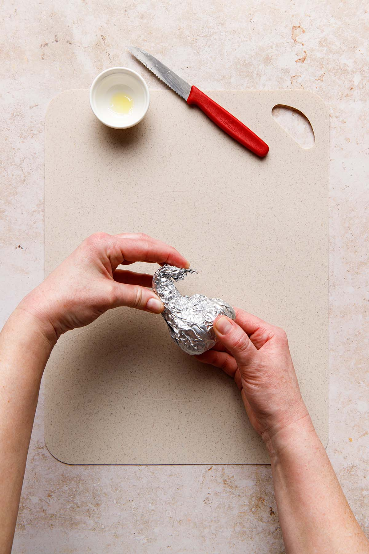 Hands wrapping a small item in aluminum foil.