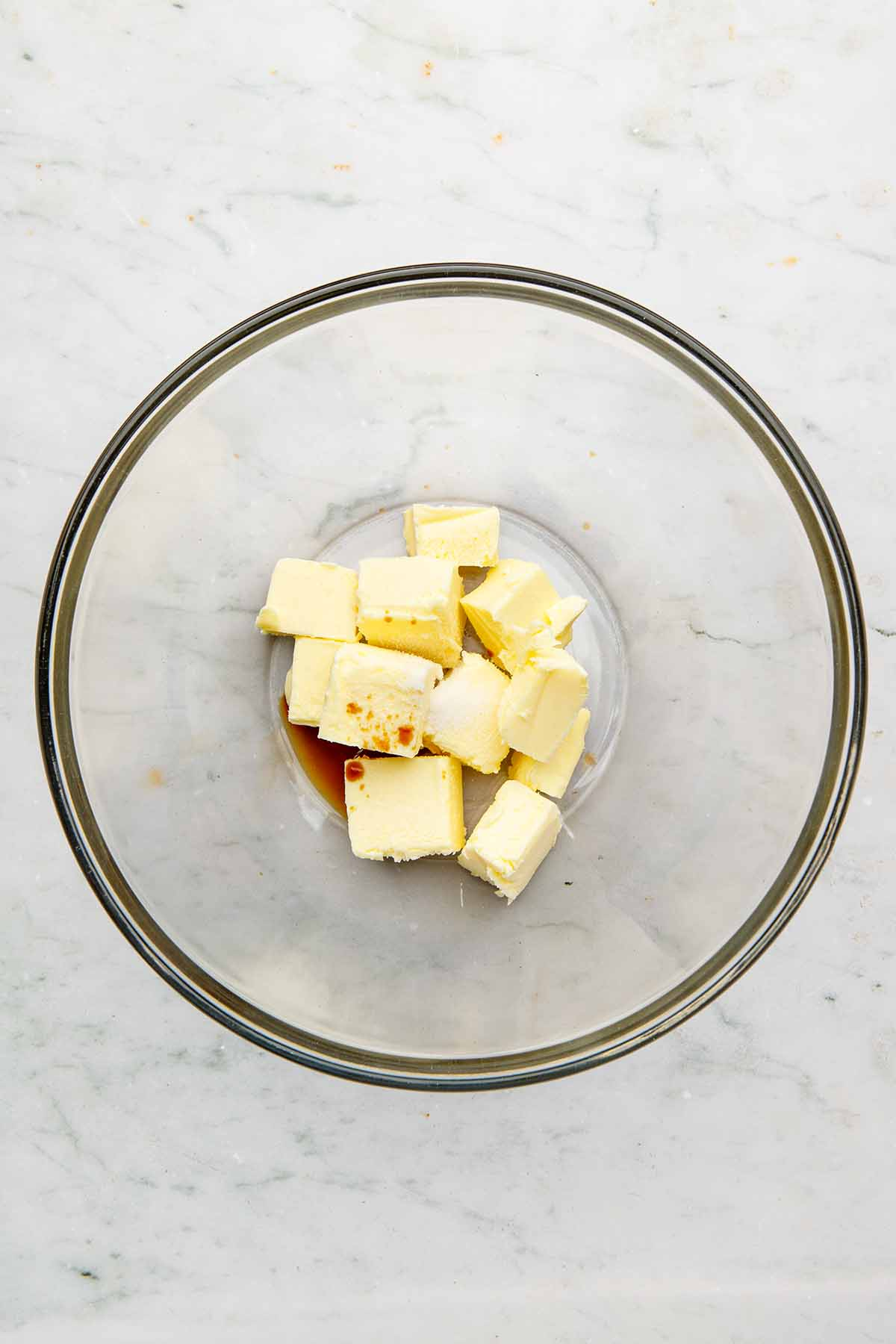 Chunks of butter, vanilla, and salt in a large glass bowl.