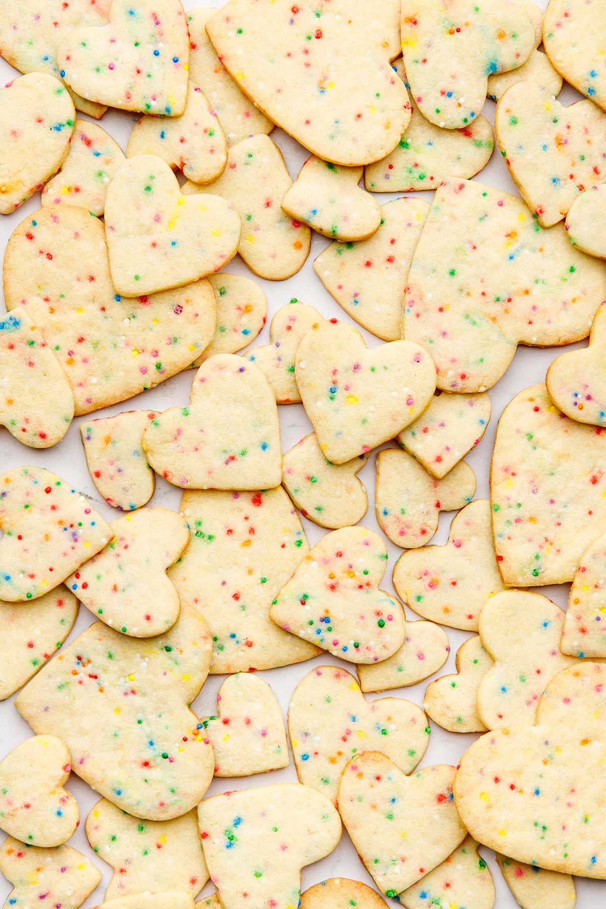Heart-shaped sugar cookies with sprinkles scattered together over a marble surface.